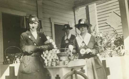 Black and white photograph of Evelyn Lightner (at left) and Red Cross workers distributing food, c.1918.