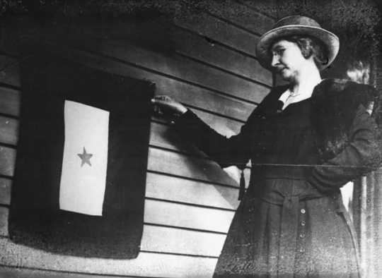 Black and white photograph of Mrs. J. P. Mohan, Gold Star mother, with flag, St. Paul, 1918.