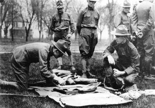 Black and white photograph of Candidates looking over United States Army kit at the Officers' Training Camp, Fort Snelling, 1917.