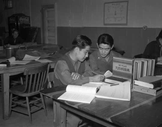Black and white photograph of MISLS students Isami Osato and George Sakanari translating Japanese civil service regulations into English at Fort Snelling, c.1944.