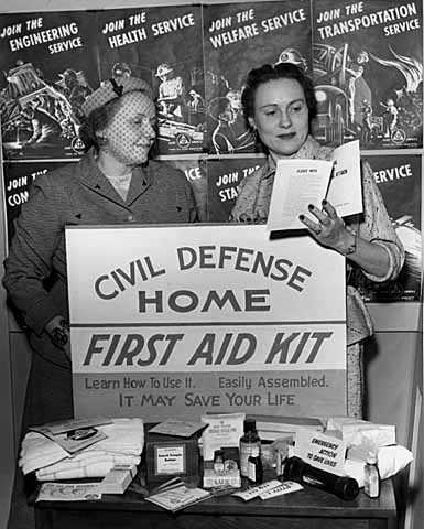 Black and white photograph of women with civil defense home first aid kit display, 1954.