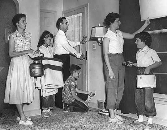 Black and white photograph of the Gerlach family at their home during a civil defense drill,1956.
