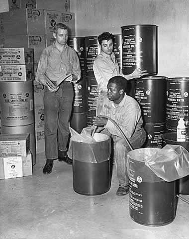Black and white photograph of people stocking fallout shelter at St. Casimir's School, St. Paul, 1962.