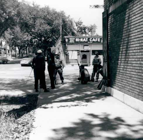 Police standing near a building on Plymouth Avenue in Near North Minneapolis during an episode of civil unrest in the neighborhood, ca. 1967. Photo by Twiggs.