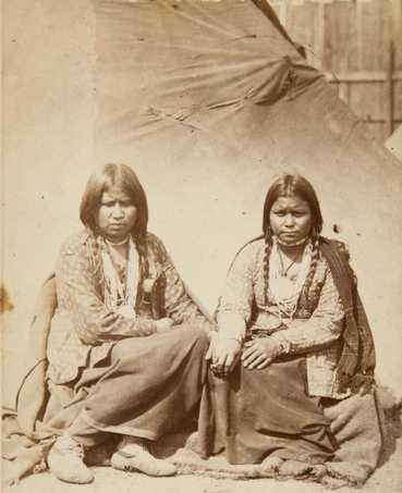 Black and white photograph of two Dakota women at the Fort Snelling concentration camp, c.1862–1863. Photograph by Joel Emmons Whitney.