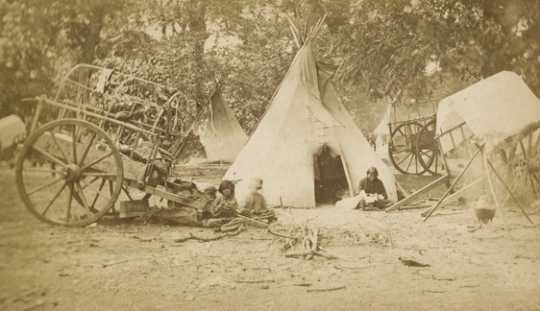 Black and white photograph of a Red River cart at a Dakota family's camp, ca. 1870.