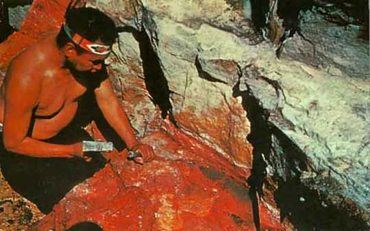 Color image of Standing Eagle working the sacred pipestone in a quarry at the Pipestone National Monument, ca. 1970.