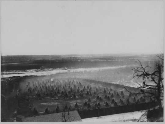 Photograph of captured Dakota in a fenced enclosure on the Minnesota River below Fort Snelling. Photographed c.1863 by Benjamin Franklin Upton.