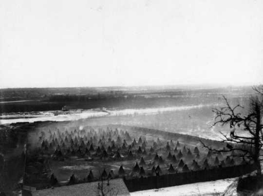 Black and white photograph of the the Dakota concentration camp on the river flats below Fort Snelling, c.1862–1863.