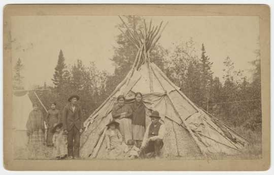 Group of Ojibwe in front of a wigwam at Grand Portage