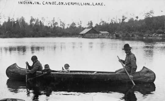 Black and white photograph of an Ojibwe family in canoe on Lake Vermilion, ca. 1905.