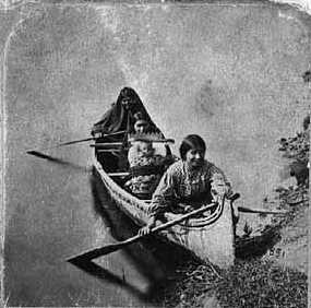 Photograph of Ojibwe women gathering wild rice c.1885.