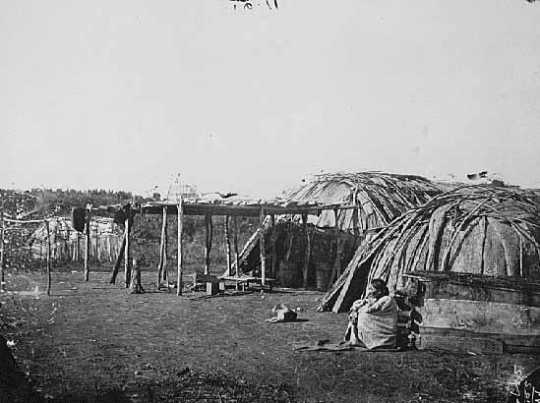 Black and white photograph of a Ho-Chunk woman sitting outside a shelter. Taken by Benjamin Franklin Upton in 1858.