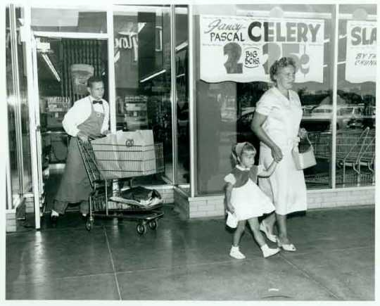 Employee Dick Liecting pushing a grocery cart for two shoppers at the Red Owl Store, Southdale Mall, Edina.