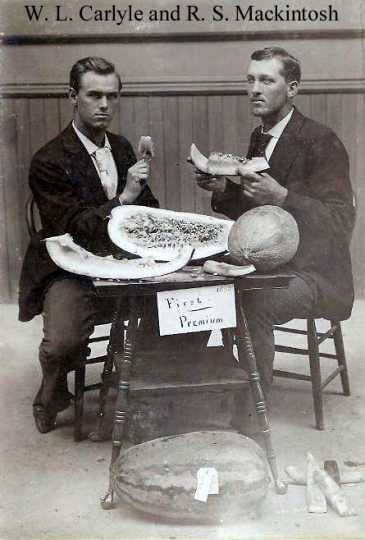 Black and white photograph of W. L. Carlyle and R. S. Mackintosh eating watermelon that was awarded first premium probably at the Minnesota State Fair, 1895.
