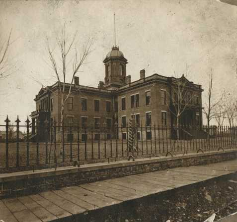 Black and white photograph of the first capitol building, ca. 1873.