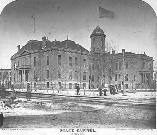 Black and white photograph of the first State Capitol building showing enlargement of 1878. Painted by Alfred Palmquist & Company, 1879.
