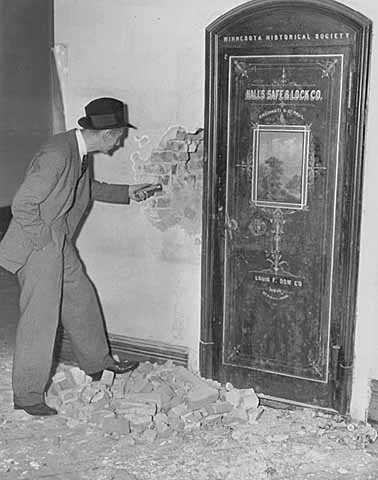 Black and white photograph of Richard Sackett examining the Minnesota Historical Society vault door in the second capitol building prior to its demolition, 1937.