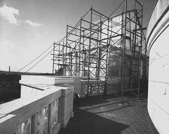 Black and white photograph of the Quadriga encased in scaffolding during application of gold leaf, 1979. Photographed by Elizabeth M. Hall.