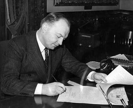 Black and white photograph of Harold Stassen signing a bill into law, 1941.