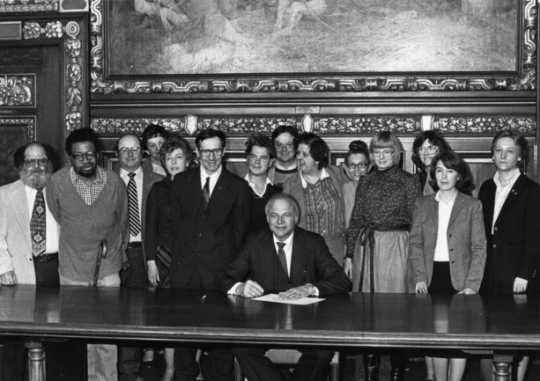 Black and white photograph of Governor Al Quie, legislators (including Allan Spear, third from left), and constituents with disabilities, ca. 1980.