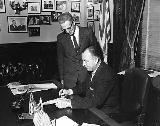 Black and white photograph of Governor Elmer Benson signing a bill with Grange Master William B. Pearson looking on, 1963. Photographed by Eugene Debs Becker.