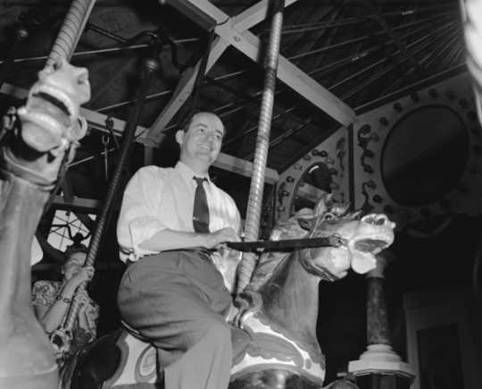 Black and white photograph of Hubert Humphrey riding the merry-go-round at the Minnesota State Fair, 1947.