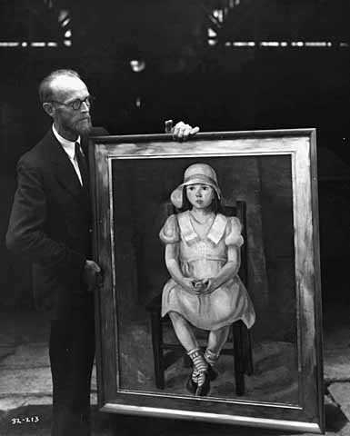 Black and white photograph of Knute Heldner holding a painting created by Elsa Jemne for the WPA Federal Art Project and exhibited at the Minnesota State Fair, c.1936.
