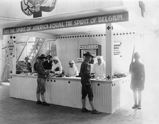 "Black and white photograph of a Red Cross booth (""Let the Spirit of America Equal the Spirit of Belgium"") at the 1917 Minnesota State Fair."