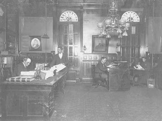 Minnesota governor's suite during John Lind's administration, c.1900. Pictured: John Lind at his desk; G. P. Wade, postmaster of the Legislature; L. A. Rosing, private secretary to the governor; and an unidentified woman.