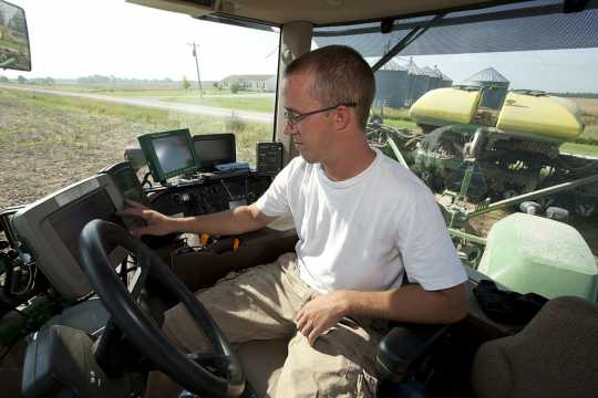 Color image of a farm worker adjusting GPS equipment inside the cab of a planter, June 25, 2009. Used courtesy of the United Soybean Board.