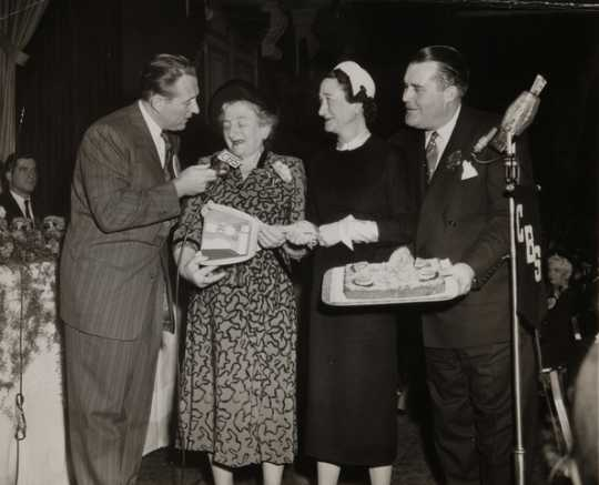 Black and white photograph from the Grand National Bake-Off at the Waldorf Astoria, New York, 1950. Left to right: Art Linkletter, contestant, Duchess of Windsor (the former Wallis Simpson), Philip Pillsbury.