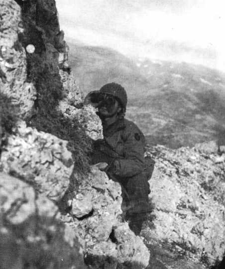 Black and white photograph of a Thirty-fourth Infantry Division officer scanning German movements on the approach to Casino, 1944.