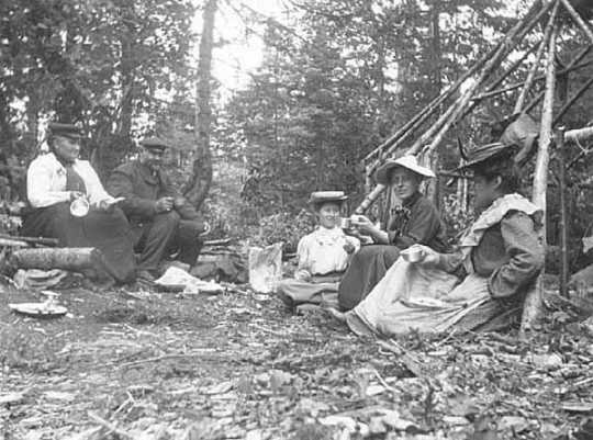 Black and white photograph of Frances Densmore seated on ground with others at Pigeon River, c. 1905.