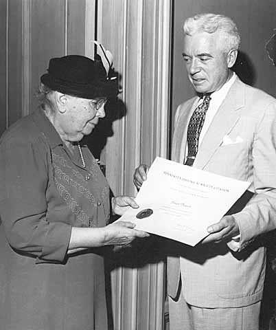 Black and white photograph of Frances Densmore being presented with citation by Harold Dean Carter.