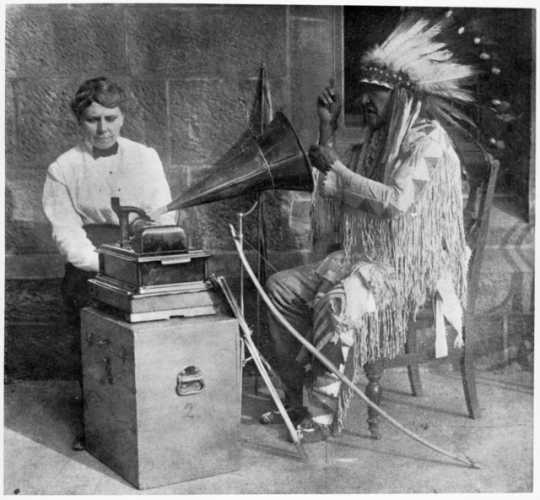 Black and white photograph of Frances Densmore with Mountain Chief who is interpreting a recording.