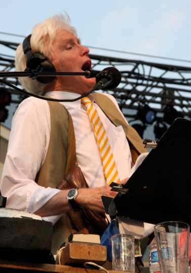 Sound effects artist Fred Newman creates sound with his mouth and other everyday objects during a live broadcast of A Prairie Home Companion from Macalester College in St. Paul, July 2015. Photograph by Wikimedia Commons user Jonathunder.