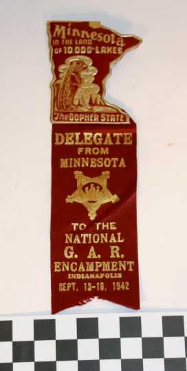 """Ribbon worn by Albert Woolson at the national Grand Army of the Republic (GAR) encampment in Indianapolis held between September 13 and 18, 1942. Attached to the maroon ribbon is a matching Minnesota pin with a gopher that reads, """"Minnesota in the Land of 10,000 lakes"""" and """"The Gopher State."""" The ribbon was donated by his daughter, Frances Campbell, to the St. Louis County Historical Society in Duluth."""