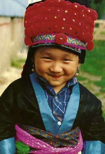 Color image of a Hmong American boy in traditional clothing. Photographed by Vue Xiong, c.1992.