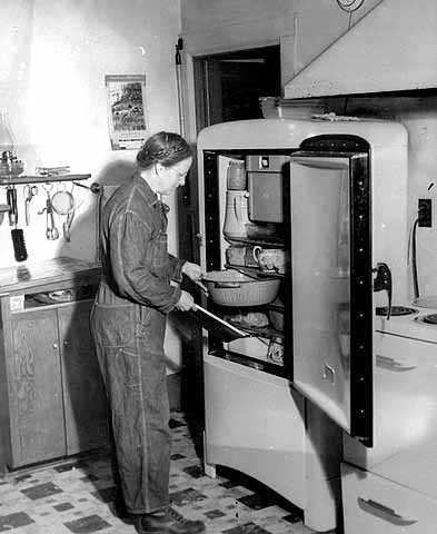 Black and white photograph of Linda Benitt at the refrigerator in her kitchen, Dakota County, 1944.