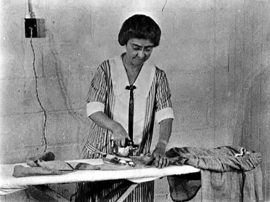 Black and white photograph of a woman on a farm ironing, ca. 1925.