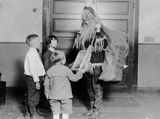 Black and white photograph of a worker dressed as Santa, passing out gifts at the Neighborhood House, c.1925.