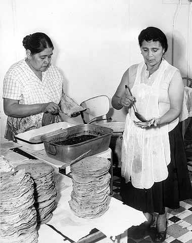 Black and white photograph of Mrs. Julio Lopez and Mrs. Francisco Rangle prepare food for an Mexican Independence celebration, Our Lady of Guadaloupe Church, September 15, 1958.