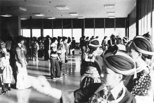 Black and white photograph of ttendees at the 1981 Hmong New Year, held in St. Paul's Highland Junior-Senior High School, participate in pov pob, a ball-toss courtship ritual. Photographed by Marlin Heise on December 19, 1981.