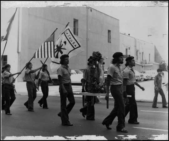Brown Berets marching with flags