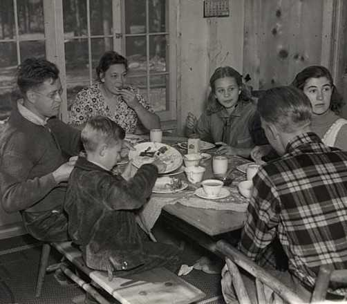 Black and white photograph of Governor Elmer Benson eating breakfast with his family at their cabin on the North shore of Lake Superior, 1937.