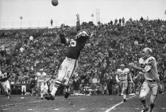 Black and white photograph of Paul Flatley catching a pass, Minnesota Vikings and Detroit Lions football game at Metropolitan Stadium Bloomington, 1963.