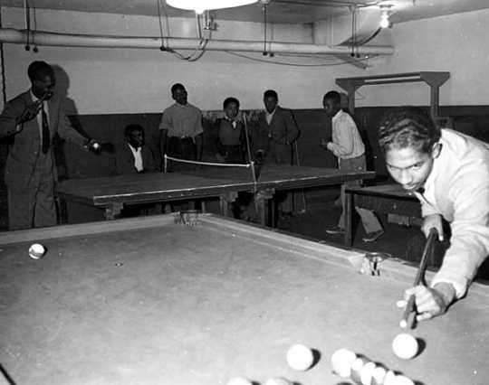 Black and white photograph of people playing table tennis and billiards at the Phyllis Wheatley House, ca. 1940.