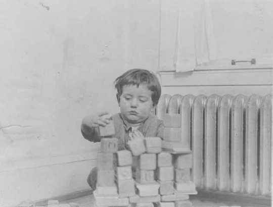 Black and white photograph of a toddler playing with blocks at the Northeast Neighborhood House, c.1925.