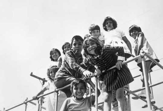 Black and white photograph of Mexican American migrant farm-worker children playing, ca. 1960.